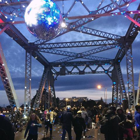 A disco ball illuminates a crowd dancing on a city bridge