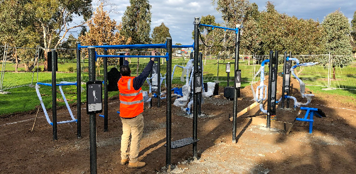 A person installing outdoor fitness equipment