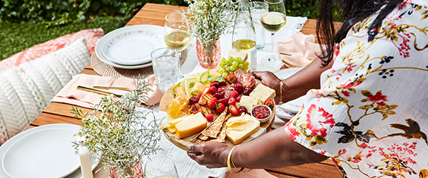 An outside picnic table set up for lunch with a cheese plate.