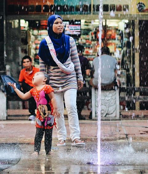 A woman and her child cool themselves under a street fountain.