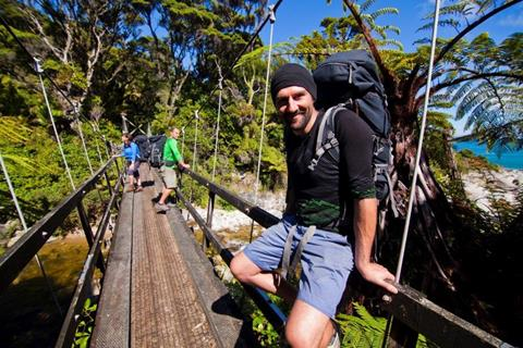 A tramper rests on a swing bridge on the Heaphy Track Great Walk (photo credit: DOC/90 seconds)