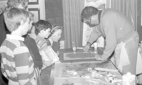 This is a 1980's image of children watching printmaker Frank Vigor. Frank is applying paint to his template to make the next print.