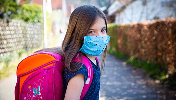 Young person with colourful COVID mask and backpack walking outside.
