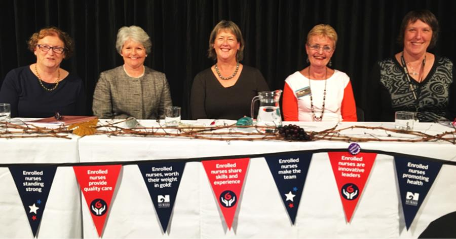 Five women sitting behind table