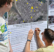 A man writes on a posterboard at a Vancouver public consultation event while a city staffer looks on.