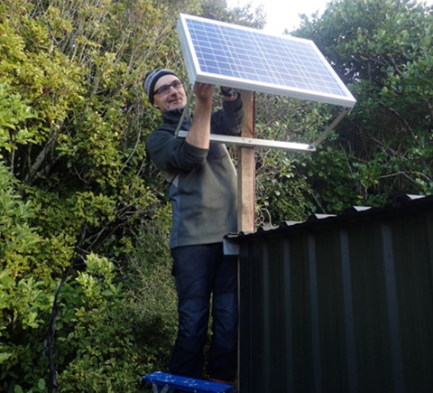 Meridian staff on Whenua Hou helping with solar panel