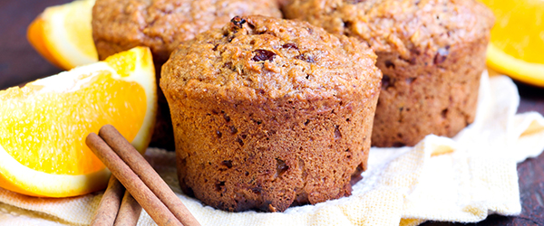 Photo of healthy cinnamon, orange, and bran muffins, with slices of fresh oranges.