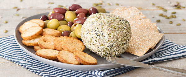 Cheese ball rolled in seeds on a serving plate with crackers, olives and a spreading knife.