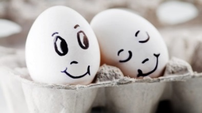 Two eggs with pen-drawn faces in an egg carton