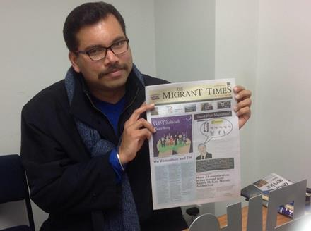 Image of Gaurav holding up a copy of 'The Migrant Times'