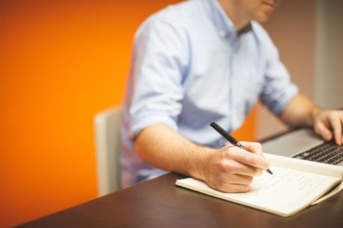 man sitting at desk with pen and paper stock photo