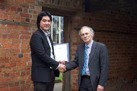 Dr Zhi Leong receiving the medal from Neil Bose