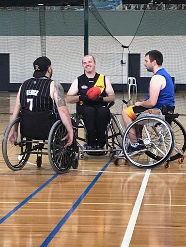 Referee and two men in wheelchairs gets ready to do the opening toss of a game of wheelchair AFL.