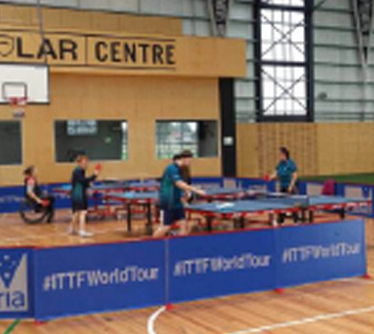 People with a range of disabilities play table tennis on three tables
