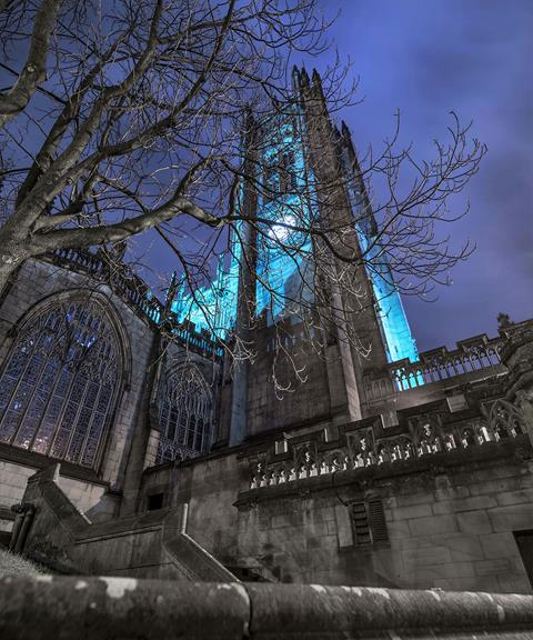 A photo of the Cathedral tower with tree branches in front of it. The photo was taken a night. the sky is dark blue and the tower is lit in a different shade of blue.