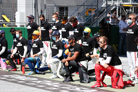 "Formula One drivers and teams kneeling with ""end racism"" shirts on"