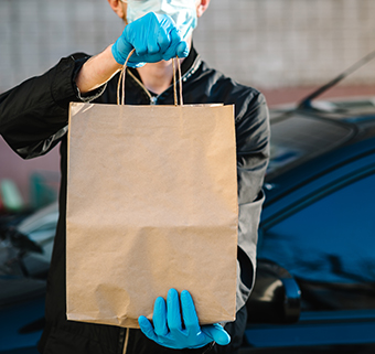 man handing off a bag while wearing a mask and gloves