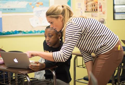 Teacher Aimee Heckman assists a student on a laptop