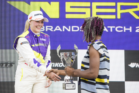 Driver shaking hand with organizer holding trophy